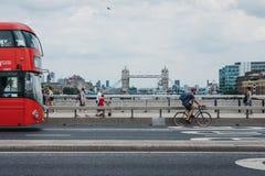 Ο ποδηλάτης, οι πεζοί και το διπλό κατάστρωμα μεταφέρουν στη γέφυρα του Λονδίνου, Λονδίνο, UK στοκ φωτογραφία