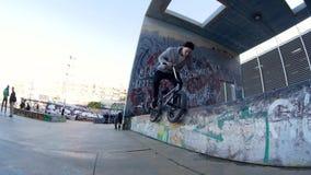 Ο ποδηλάτης τύπων BMX κάνει τις διαφορετικά περιστροφές και τα τεχνάσματα στο ποδήλατο στο αστικό περιβάλλον απόθεμα βίντεο