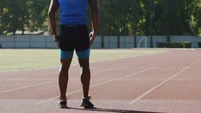 Ο ποδοσφαιριστής που κρατούν το σώμα του και οι μυ'ες τονίζουν, εκπαιδευτικός σκληρά στο στάδιο, αθλητισμός απόθεμα βίντεο