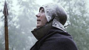 Ο πολεμιστής με το κράνος στο κεφάλι του και μια λόγχη υπό εξέταση στέκεται στη βροχή φιλμ μικρού μήκους