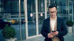 Ο πολυάσχολος εταιρικός διευθυντής κάνει μια κλήση με ένα τηλέφωνο, κλείνει επάνω απόθεμα βίντεο