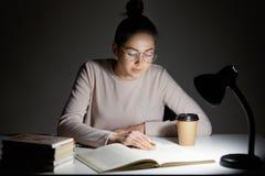 Ο πολυάσχολος θηλυκός έφηβος διαβάζει το βιβλίο, χρησιμοποιεί τον επιτραπέζιο λαμπτήρα, προετοιμάζεται για την τελική εξέταση, κά στοκ εικόνες
