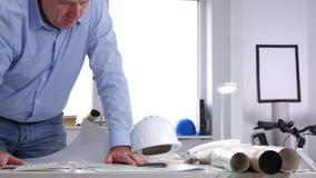 Ο πολυάσχολος μηχανικός ανοικτός και μελετά ένα σχέδιο οικοδόμησης στο γραφείο αρχιτεκτονικής απόθεμα βίντεο
