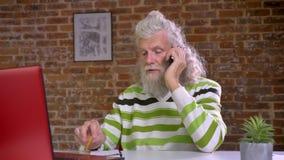 Ο πολυάσχολος χαριτωμένος καυκάσιος γενειοφόρος ηληκιωμένος κρεμά στην ψύχρα του τηλεφώνων και ομιλίας εξετάζοντας τον υπολογιστή φιλμ μικρού μήκους