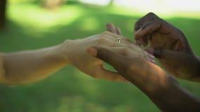 Ο πολυφυλετικός γάμος, αρσενικό χέρι βάζει το χρυσό δαχτυλίδι στο δάχτυλο νυφών, γαμήλιος χρόνος απόθεμα βίντεο