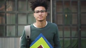 Ο πολυ-εθνικός ή πολυπολιτισμικός τύπος στέκεται μπροστά από τη κάμερα και το χαμόγελο απόθεμα βίντεο