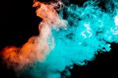 Ο πολύχρωμος, παχύς καπνός, που φωτίστηκε από το φως σε ένα σκοτεινό κλίμα, ένωσε στενά με τις λέσχες και τις μπούκλες στοκ εικόνα