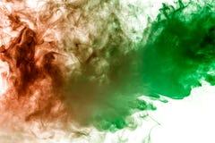 Ο πολύχρωμος, παχύς καπνός, που φωτίστηκε από χρωματισμένος σε πράσινο και το κόκκινο φως σε ένα απομονωμένο λευκό κλίμα, ένωσε σ στοκ εικόνες