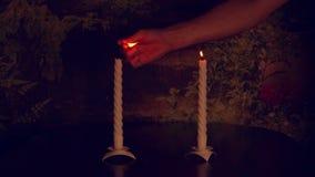 Ο πολύ σε αργή κίνηση πυροβολισμός επανδρώνει το φωτισμό χεριών από το ζευγάρι αντιστοιχιών των κεριών στο σκοτάδι Ήρεμη σκηνή Έν απόθεμα βίντεο