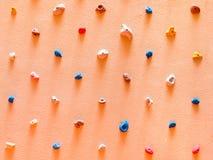 Ο πορτοκαλής τοίχος αναρρίχησης με ζωηρόχρωμο κρατά στοκ φωτογραφίες με δικαίωμα ελεύθερης χρήσης