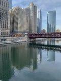 Ο ποταμός του Σικάγου απεικονίζει τη γέφυρα και τους ουρανοξύστες επάνω στην παγωμένη επιφάνεια στοκ εικόνα
