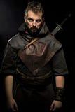 Ο πολεμιστής Βίκινγκ, αρσενικό που ντύνεται στο βάρβαρο ύφος με το ξίφος, αντέχει Στοκ Φωτογραφία