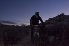 Ο ποδηλάτης κατεβαίνει το λόφο τη νύχτα Στοκ Φωτογραφία