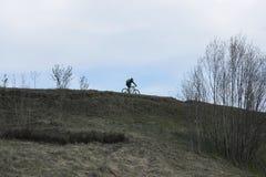 Ο ποδηλάτης κινείται πάνω από το επίπεδο λόφων ορίζοντα Στοκ Φωτογραφία