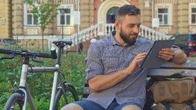 Ο ποδηλάτης κοιτάζει βιαστικά interntet στην ταμπλέτα φιλμ μικρού μήκους