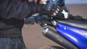 Ο ποδηλάτης στην οδό δίπλα στο ποδήλατό του, βάζει στα γάντια φιλμ μικρού μήκους