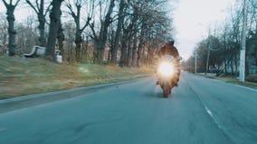 Ο ποδηλάτης στο κράνος οδηγά τη μοτοσικλέτα προς τη κάμερα κατά μήκος της περιοχής κοιτώνων πόλεων απόθεμα βίντεο