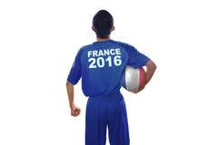 Ο ποδοσφαιριστής κρατά τη σφαίρα με μια σημαία της Γαλλίας Στοκ Εικόνες