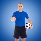 Ο ποδοσφαιριστής με μια σφαίρα φυλλομετρεί επάνω πέρα από το μπλε Στοκ Εικόνες