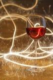 Ο πολυτελής πυροβολισμός του ροδαλού γυαλιού κρασιού στο χρυσό ακτινοβολεί Στοκ εικόνες με δικαίωμα ελεύθερης χρήσης