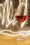 Ο πολυτελής πυροβολισμός του ροδαλού γυαλιού κρασιού στο χρυσό ακτινοβολεί Στοκ Εικόνα