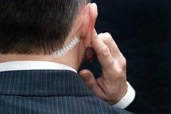 Ο πράκτορας Μυστικής Υπηρεσίας ακούει το ακουστικό, πίσω Στοκ Φωτογραφία