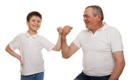 Ο πρεσβύτερος και τα παιδιά παρουσιάζουν χέρια μυών Στοκ Εικόνες
