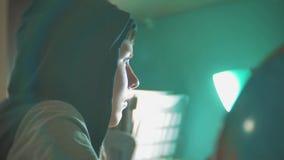 Ο προγραμματιστής ατόμων χάκερ στην κουκούλα που χρησιμοποιεί τον υπολογιστή για τις πληροφορίες αμυχών και τα στοιχεία από το χρ φιλμ μικρού μήκους