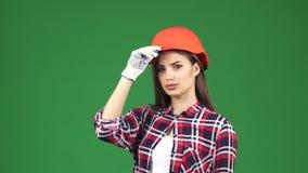 Ο προκλητικός νέος θηλυκός ανάδοχος που φορά hardhat την παρουσίαση φυλλομετρεί επάνω απόθεμα βίντεο