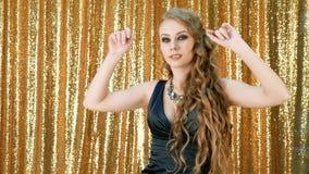 Ο προκλητικός χρυσός κομμάτων γυναικών χορεύοντας ακτινοβολεί υπόβαθρο φιλμ μικρού μήκους