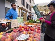 Ο προμηθευτής και η γυναίκα μιλούν πέρα από τα ροδάκινα και άλλα φρούτα για την πώληση στην υπαίθρια αγορά στη γαλλική πόλη του b Στοκ Εικόνες