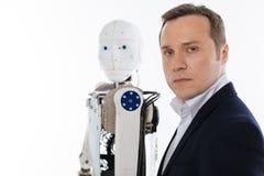 Ο προοδευτικός εφευρέτης και το ρομπότ του που στέκονται στο ίδιο πράγμα θέτουν Στοκ φωτογραφία με δικαίωμα ελεύθερης χρήσης