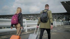 Ο προσεγγισμένοι άνδρας και η γυναίκα περπατούν πέρα από την πλατφόρμα σιδηροδρόμων, που κυλά τις βαλίτσες απόθεμα βίντεο