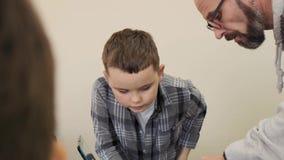 Ο προσεκτικός δάσκαλος παρουσιάζει στο μικρό σπουδαστή του πώς να σχεδιάσει το πλαστικό μηχανικό αυτοκίνητο σε αργή κίνηση απόθεμα βίντεο