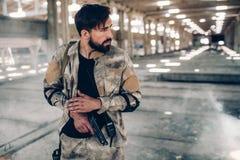 Ο προσεκτικός και σοβαρός νεαρός άνδρας κοιτάζει στο δικαίωμα Φορά ειδικό ομοιόμορφο Επίσης ο τύπος έχει το μικρό πυροβόλο όπλο σ Στοκ φωτογραφία με δικαίωμα ελεύθερης χρήσης