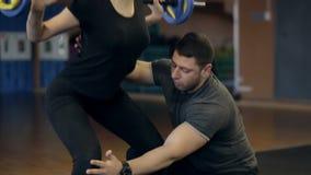 Ο προσωπικός εκπαιδευτής διδάσκει το κορίτσι για να κάνει μια άσκηση με το barbell στους ώμους της απόθεμα βίντεο