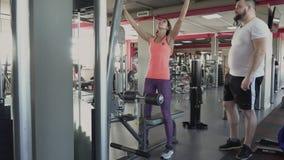 Ο προσωπικός εκπαιδευτής παρουσιάζει άτομο πώς να κάνει την άσκηση στον προσομοιωτή στη γυμναστική Ο τύπος πρόκειται να ταλαντευθ απόθεμα βίντεο