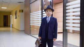 Ο προϊστάμενος παιδάκι με το χαρτοφύλακα στο μεγάλο γραφείο απόθεμα βίντεο