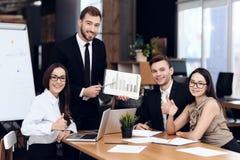 Ο προϊστάμενος της επιχείρησης μιλά με άλλους υπαλλήλους κατά τη διάρκεια της συνεδρίασης στοκ εικόνα