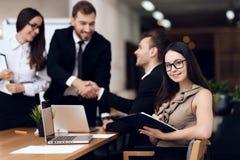 Ο προϊστάμενος της επιχείρησης τινάζει τα χέρια με έναν άλλο υπάλληλο κατά τη διάρκεια της συνεδρίασης στοκ εικόνα