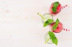 Ο πρόσφατα συνδυασμένος πράσινος και κόκκινος καταφερτζής φρούτων στα βάζα γυαλιού με το άχυρο, μέντα βγάζει φύλλα, τοπ άποψη Στοκ Εικόνες
