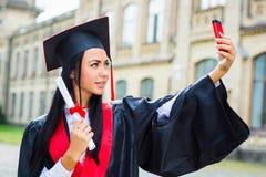Ο πτυχιούχος κοριτσιών παίρνει selfie τη φωτογραφία με το smartphone Στοκ Εικόνες