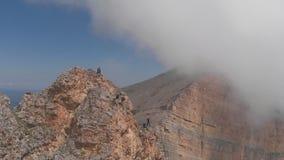 Ο πυροβολισμός κηφήνων ενός συγκίνηση-αναζητητή πηδά από έναν απότομο βράχο με ένα σχοινί φιλμ μικρού μήκους