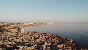 Ο πυροβολισμός κηφήνων της δύσκολης παραλίας απότομων βράχων με το άσπρο μνημείο στην πόλη της Πάφος Κύπρος με την ηρεμία βλέπει  απόθεμα βίντεο