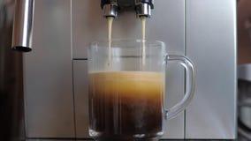 Ο πυροβολισμός κινηματογραφήσεων σε πρώτο πλάνο από τον κατασκευαστή μηχανών ή καφέ Espresso χύνει τον καφέ στο φλυτζάνι γυαλιού απόθεμα βίντεο