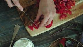 Ο πυροβολισμός κινηματογραφήσεων σε πρώτο πλάνο ενός χεριού γυναικών ` s προετοιμάζεται από το τυρί και τα λαχανικά ψωμιού για έν απόθεμα βίντεο