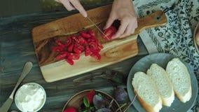 Ο πυροβολισμός κινηματογραφήσεων σε πρώτο πλάνο ενός χεριού γυναικών ` s προετοιμάζεται από το τυρί και τα λαχανικά ψωμιού για έν φιλμ μικρού μήκους