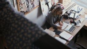 Ο πυροβολισμός φωτογραφικών διαφανειών του σχεδιαστή σύρει τα σκίτσα στο στούντιο Σχεδιαστής χώρου εργασίας απόθεμα βίντεο