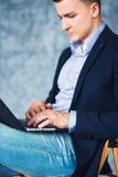 Ο πυροβολισμός του κομψού επιχειρηματία με την πρόθεση φαίνεται εργαζόμενος στο lap-top Στοκ Φωτογραφία