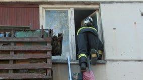 Ο πυροσβέστης αναρριχείται επάνω σε ένα παράθυρο διαμερισμάτων για να σώσει τους ανθρώπους Μια πυρκαγιά σε μια πολυκατοικία φιλμ μικρού μήκους